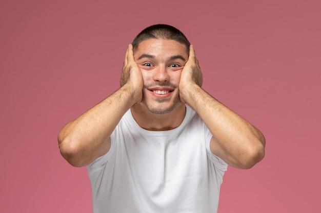 Giovane maschio di vista frontale in camicia bianca che posa con l'espressione incoraggiante su fondo rosa
