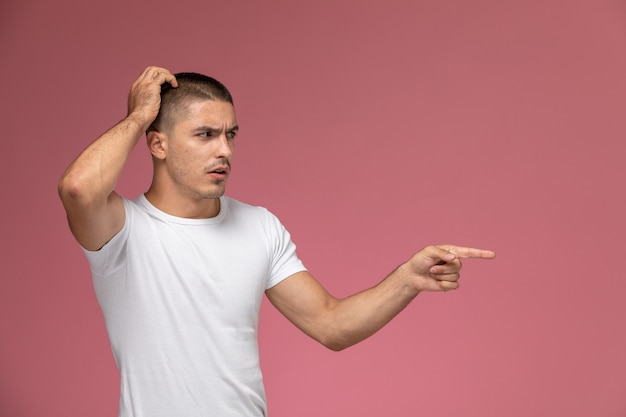 Front view young male in white shirt posing with confused expression on the pink background