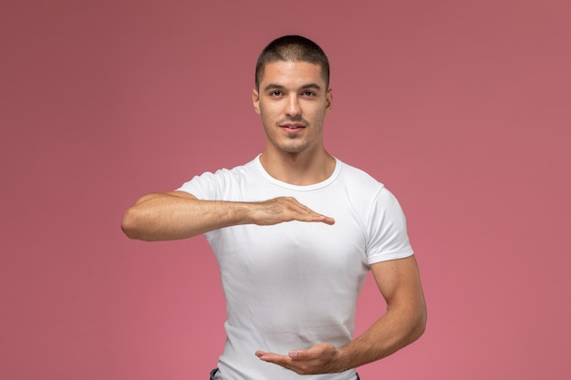 Front view young male in white shirt posing with his hands on the pink background