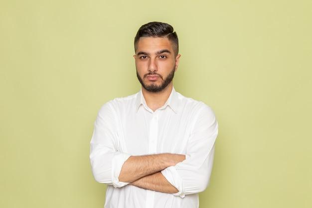 Un giovane maschio di vista frontale nella posa bianca della camicia