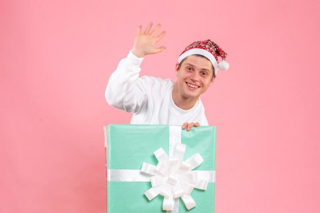 Vista frontale giovane maschio in camicia bianca con presente sorridente e saluto su sfondo rosa