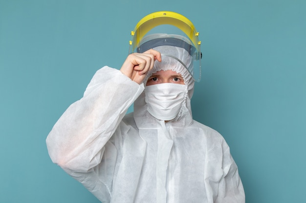 A front view young male in white special suit taking off special head mask on the blue wall man suit danger special equipment color