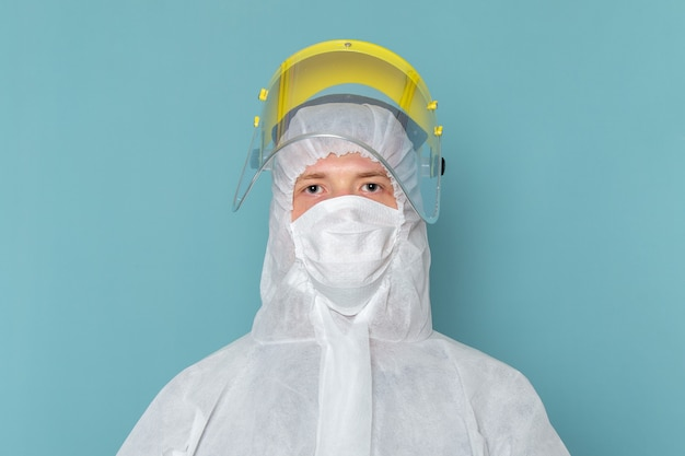 A front view young male in white special suit wearing special head mask on the blue wall man suit danger special equipment color