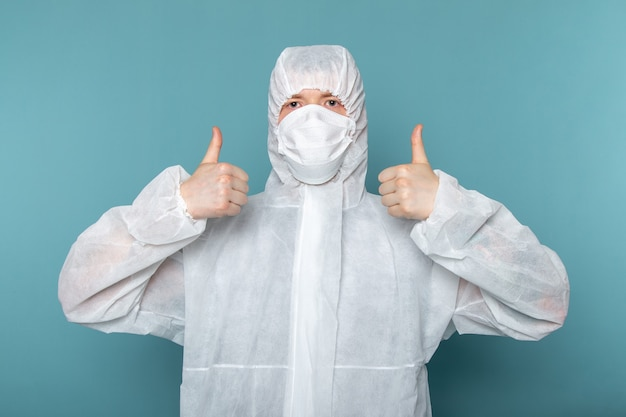 A front view young male in white special suit wearing sterile protective mask on the blue wall man suit danger special equipment color