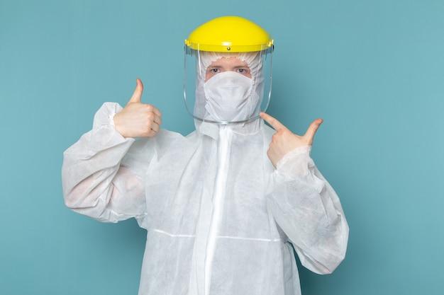 Un giovane maschio di vista frontale in vestito speciale bianco che porta maschera capa speciale gialla sul colore blu dell'attrezzatura speciale del pericolo del vestito dell'uomo della parete