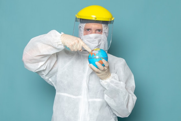 A front view young male in white special suit and yellow special helmet holding globe on the blue wall man suit danger special equipment color