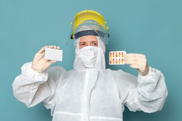 A front view young male in white special suit and yellow special helmet holding pills and white card on the blue wall man suit danger special equipment color