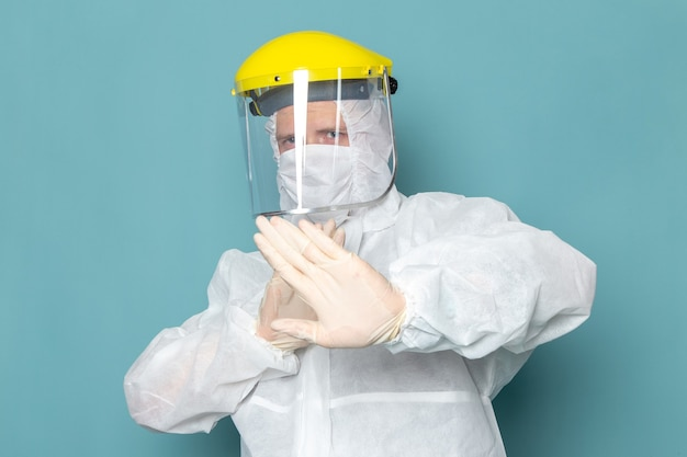A front view young male in white special suit and yellow special helmet keeping distance on the blue wall man suit danger special equipment color