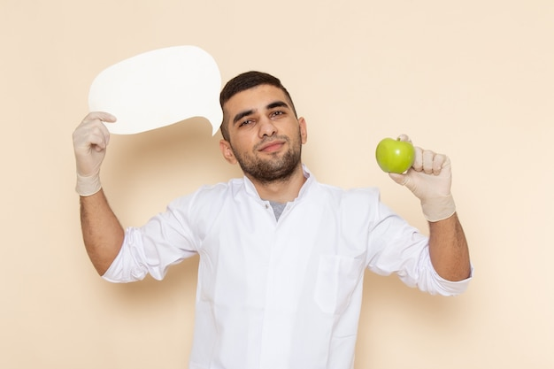 Front view young male in white suit wearing gloves holding white sign and apple on beige