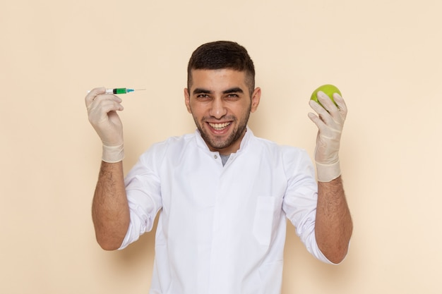 Front view young male in white suit wearing gloves injecting apple laughing on beige