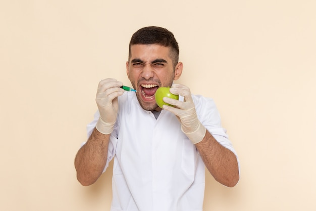 Front view young male in white suit wearing gloves injecting apple screaming on beige