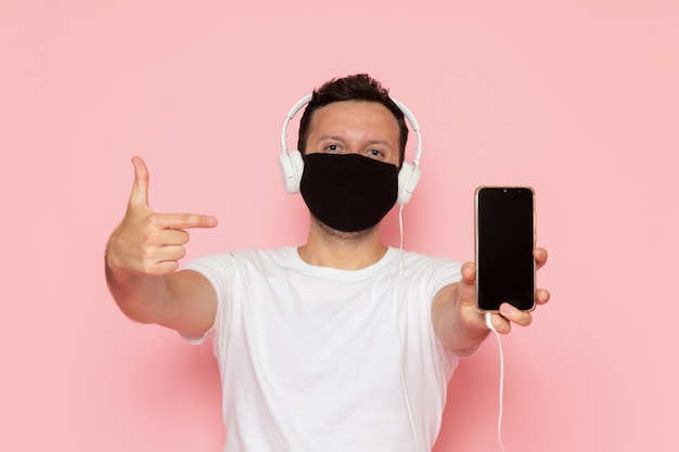 A front view young male in white t-shirt black mask listening to music through earphones on the pink desk man color emotion pose
