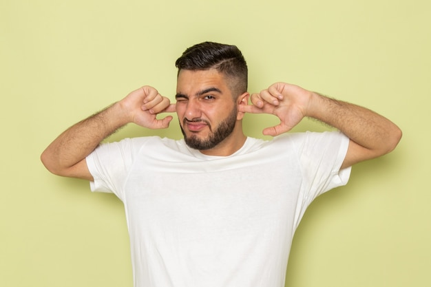A front view young male in white t-shirt covering his ears