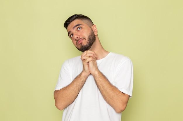 Un giovane maschio di vista frontale nel sogno ad occhi aperti della maglietta bianca