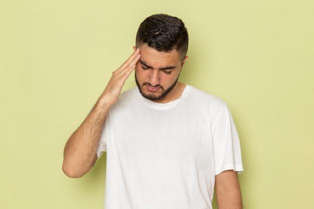 Un giovane maschio di vista frontale in maglietta bianca che ha un'emicrania