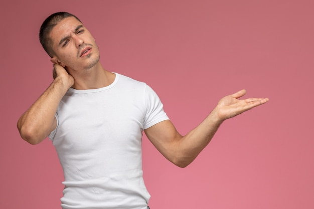 Front view young male in white t-shirt having a neck ache on pink background