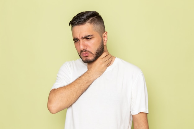 Un giovane maschio di vista frontale in maglietta bianca che ha problemi alla gola