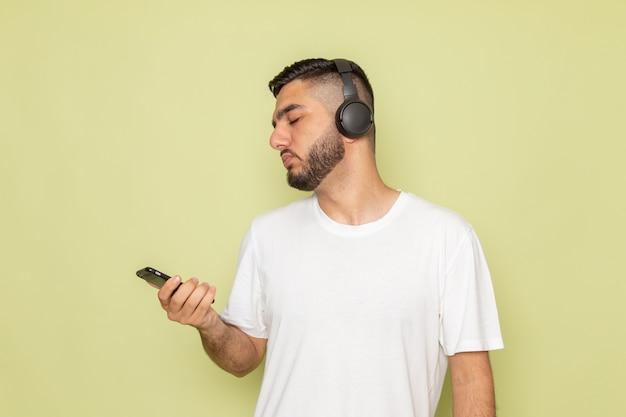 Un giovane maschio di vista frontale in t-shirt bianca che tiene telefono e ascolto di musica