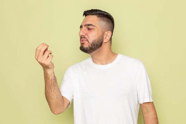 Un giovane maschio di vista frontale in maglietta bianca che tiene il modello di posa