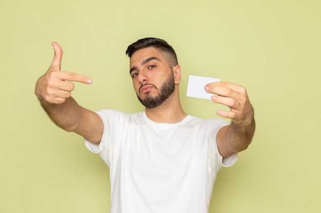 Un giovane maschio di vista frontale in maglietta bianca che tiene carta bianca
