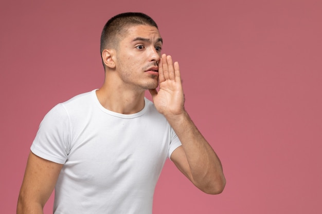 Front view young male in white t-shirt just whispering on pink background