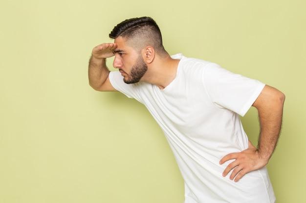 Un giovane maschio di vista frontale in maglietta bianca che esamina la distanza