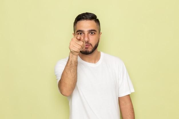 Un giovane maschio di vista frontale in maglietta bianca che indica