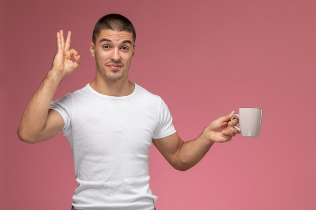 Front view young male in white t-shirt posing and holding cup of coffee on pink background
