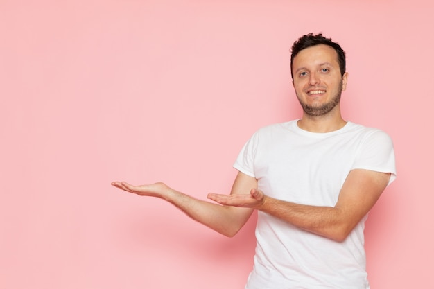A front view young male in white t-shirt posing and smiling on the pink wall man color pose