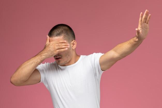 Giovane maschio di vista frontale in maglietta bianca che posa con la faccia coperta su fondo rosa