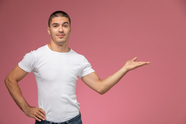 Front view young male in white t-shirt posing with raised hand and palm on pink background