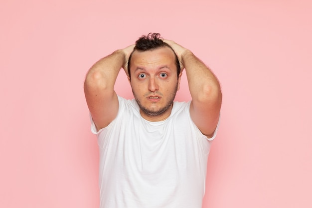 A front view young male in white t-shirt posing with surprised expression