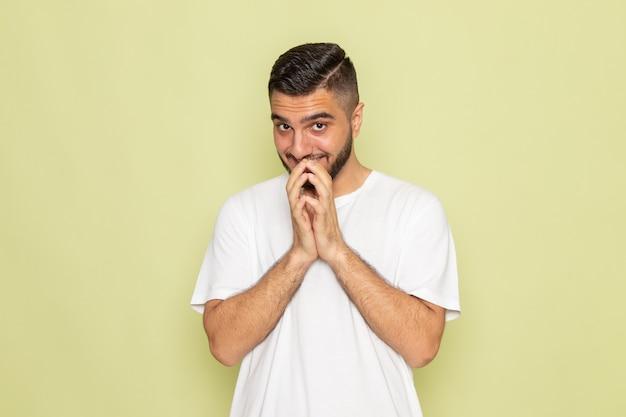 Un giovane maschio di vista frontale nella posa bianca della maglietta