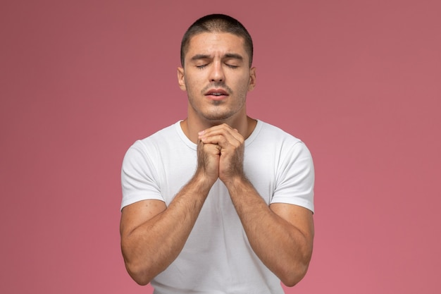 Front view young male in white t-shirt in prayer posing on pink background