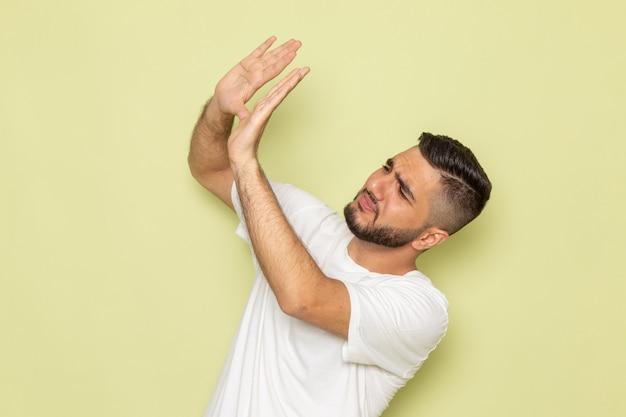 Un giovane maschio di vista frontale in maglietta bianca spaventato di qualcosa