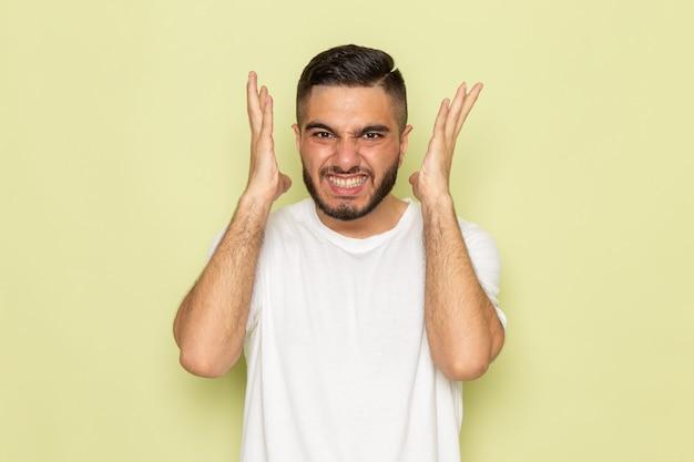 Un giovane maschio di vista frontale in maglietta bianca che mostra le emozioni