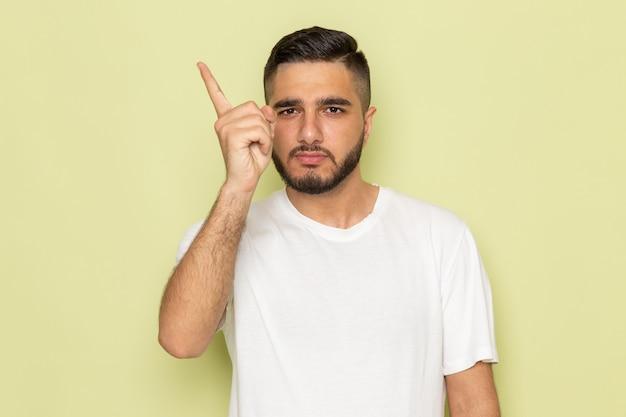 Un giovane maschio di vista frontale in maglietta bianca che mostra il suo dito
