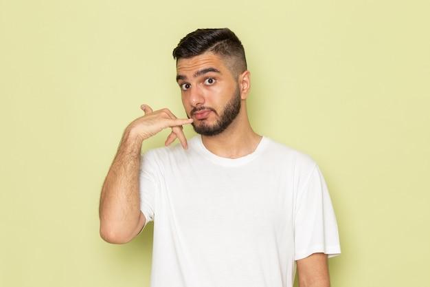 Un giovane maschio di vista frontale in maglietta bianca che mostra il segnale di chiamata telefonica