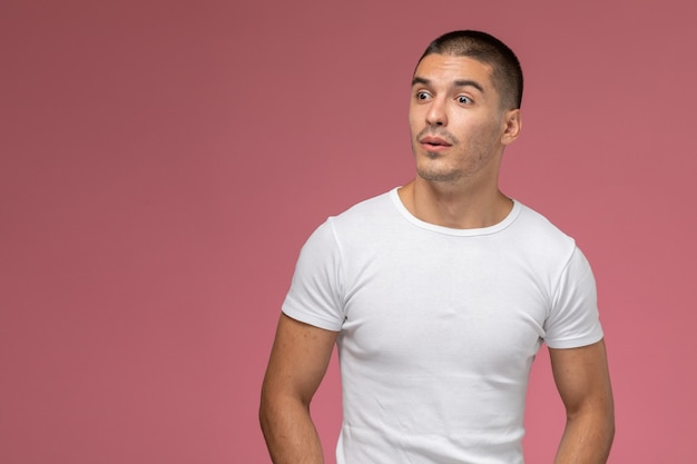 Front view young male in white t-shirt simply posing on the pink background