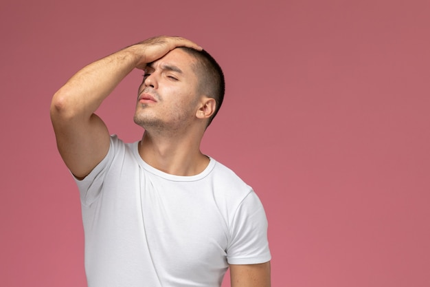 Front view young male in white t-shirt stressed and holding his head on pink background