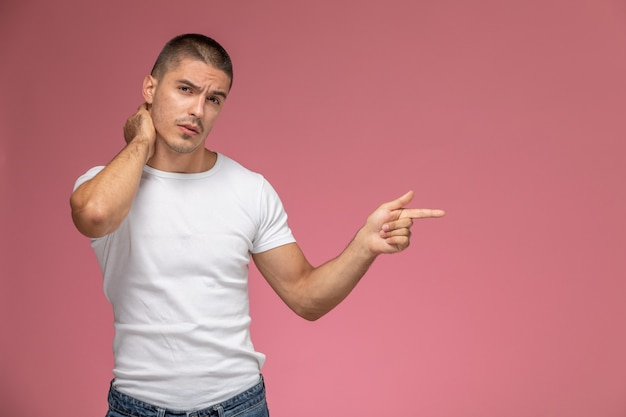 Front view young male in white t-shirt suffering from neck ache on pink desk
