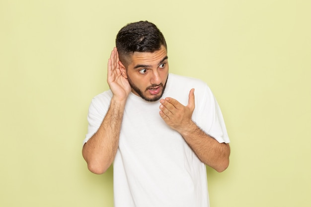 Un giovane maschio di vista frontale in maglietta bianca che prova a sentire fuori