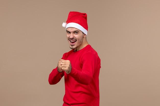 갈색 배경 크리스마스 감정 휴일에 화난 표정으로 전면보기 젊은 남성