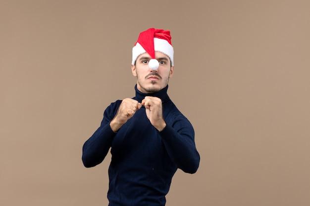 茶色の机の感情のクリスマス休暇に怒っている表情を持つ若い男性の正面図