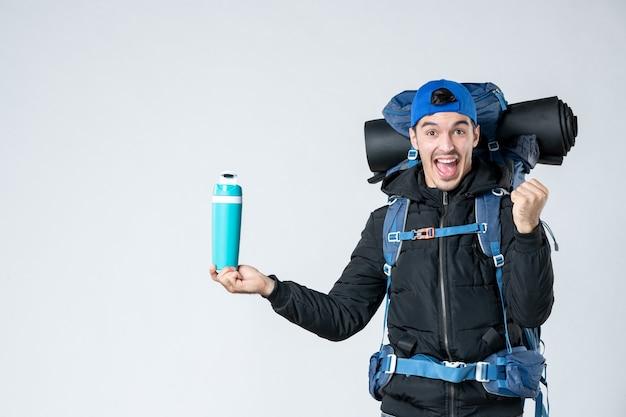 正面図白い背景にバックパックと魔法瓶を持つ若い男性自然キャンペーン山の冷たい森の空気感情スノーキャンプ