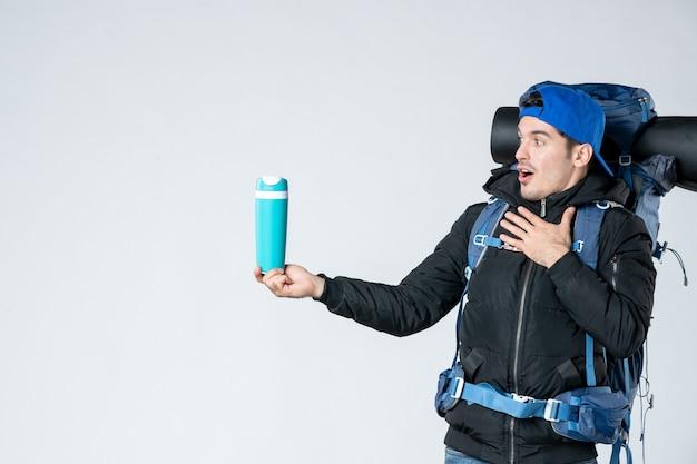 正面図白い背景にバックパックと魔法瓶を持つ若い男性自然キャンペーン山の冷たい森のエアテントスノーキャンプ