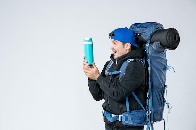 正面図白い背景にバックパックと魔法瓶を持つ若い男性雪の森自然冷気テント山キャンペーン