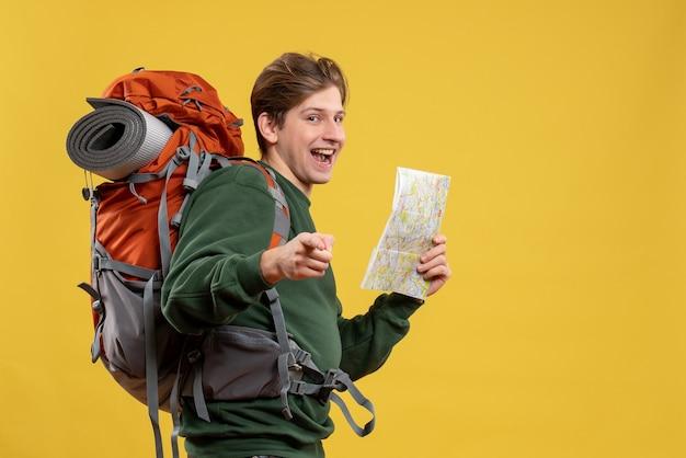 Vista frontale giovane maschio con zaino in possesso di mappa