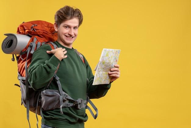 地図を保持しているバックパックを持つ若い男性の正面図 無料写真