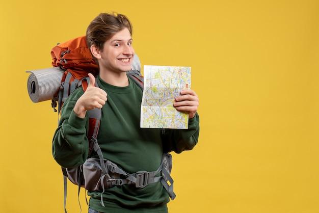 地図を保持しているバックパックを持つ若い男性の正面図